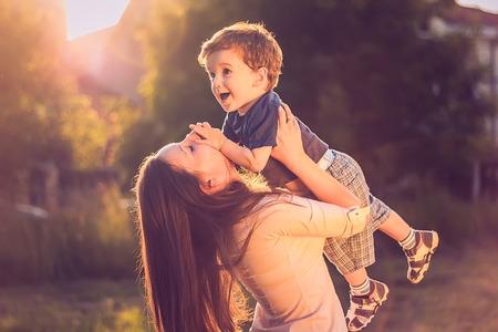 mamma e figlio: Madre che alza il suo figlio in su