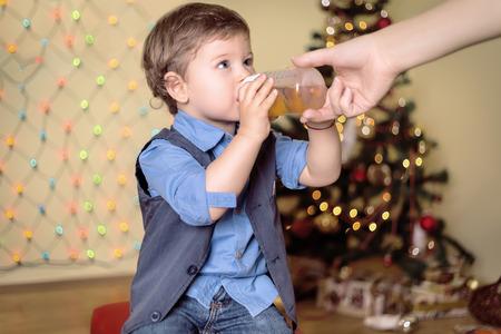 pelo castaño claro: Madre da una botella a su hijo en una víspera de Navidad