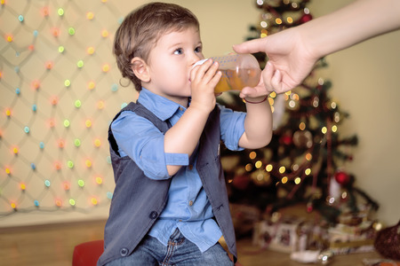 light brown eyes: Mother gives a bottle to her son on a christmas eve Stock Photo
