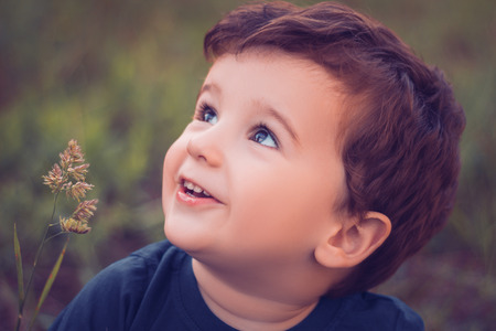 brown hair blue eyes: Boy looking up and smiling