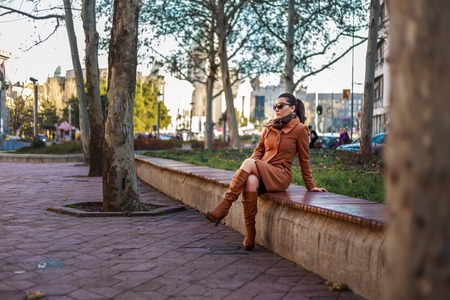 leather boots: Fashionable girl sitting on a bench Stock Photo