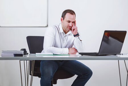 chairman: Businessman thinking in front of laptop