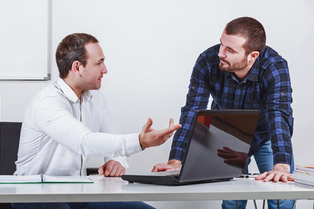 Two businessmen  discuss at meeting in office