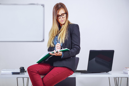 Businesswoman writing notes and sitting on desk photo