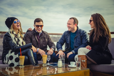Two couples laughing outdoors