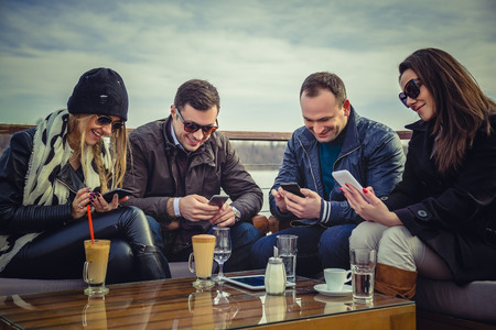 A group of people looking at a cell phone and laughing