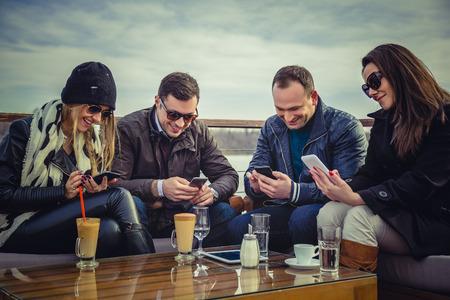 riendose: Un grupo de personas que buscan en un tel�fono celular y la risa Foto de archivo