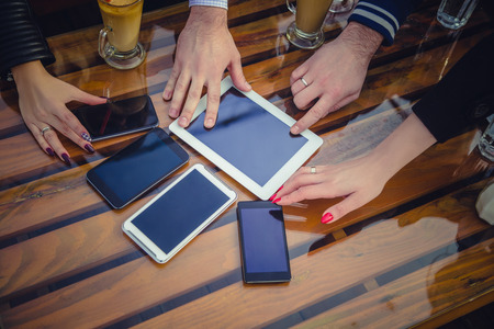 Hands reaching for mobile phones and tablet Stock Photo