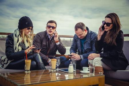 čtyři lidé: Skupina lidí pomocí mobilního telefonu Reklamní fotografie