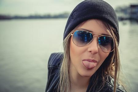 lengua afuera: Muchacha de moda que muestra la lengua Foto de archivo