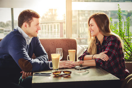 25 29: Romantic couple holding hands at coffee shop Stock Photo