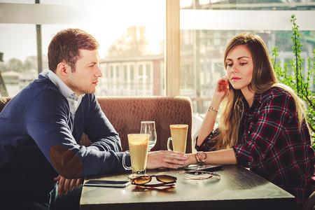 novios enojados: Sad rom�ntica pareja cogidos de la mano en la tienda de caf� Foto de archivo