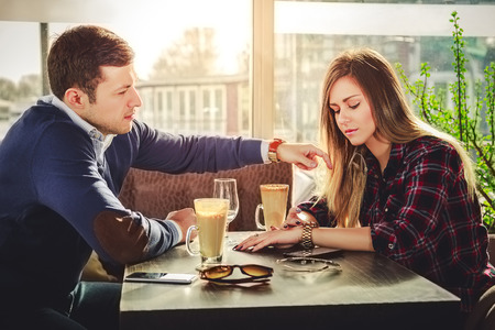 Girl is looking at watch while he is touching her hair Stockfoto