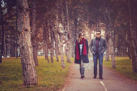 autumn city: Happy couple walking in autumn city park