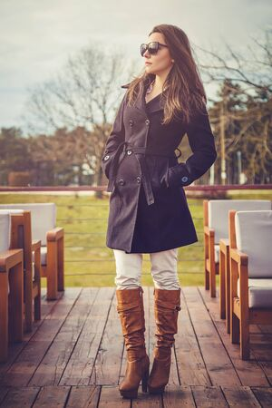 girl boots: fashion style portrait of young trendy girl standing in the sun