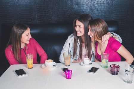 Three young girls having fun in a cafe