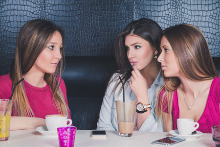Three young girls having serious conversation in a cafe