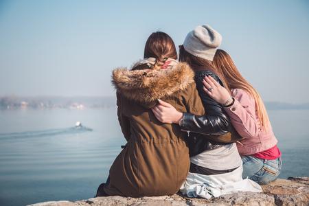 Three girlfriends looking at river boat Stockfoto