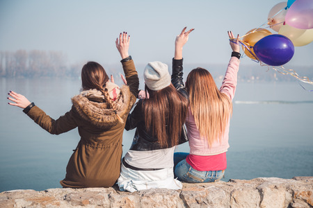 Ecstatic girls waving on river bank