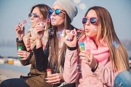 fun day: Girlfriends blowing soap bubbles Stock Photo