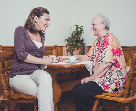 taza cafe: Nieta y abuela riendo Foto de archivo