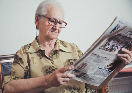 Older woman eelaxing and reading newspaper