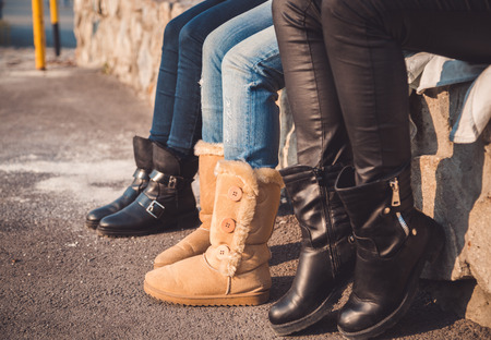 Three pairs of girls legs with boots on them Фото со стока