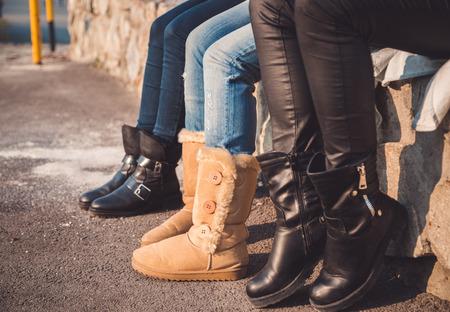 Tre paia di ragazze gambe con gli stivali su di essi