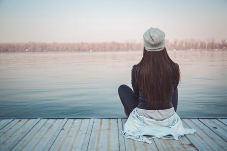 Menina sentada no cais e lookingat do rio