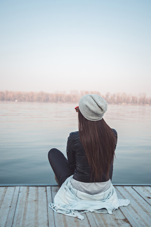 Girl sitting on pier and lookingat the river Stock Photo - 40838946
