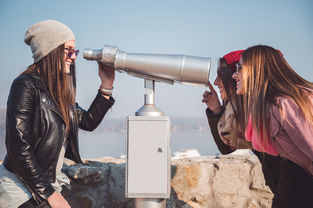 fooling: Girls fooling around with panorama binoculars telescope Stock Photo