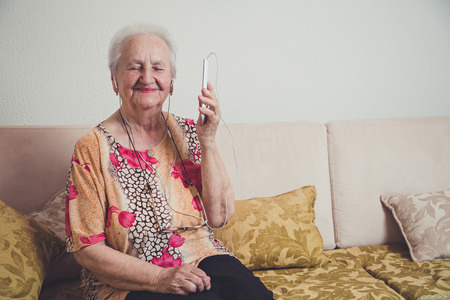 abuela: Mujer escuchando música mayor en un teléfono móvil