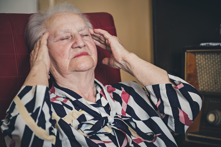 radio activity: Senior woman having headache
