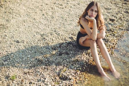 Muchacha aburrida con los con los pies en la playa y mirando a lo lejos