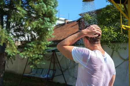 hair back: Handsome man from the back showering outside Stock Photo