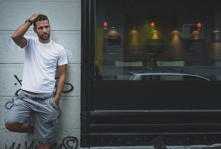 Handsome man posing on a wall Standard-Bild