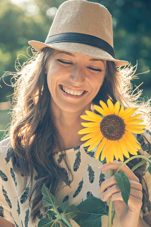 Girl holding sunflower an smiling