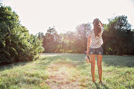 green back: Girl standing in park looking at the sun