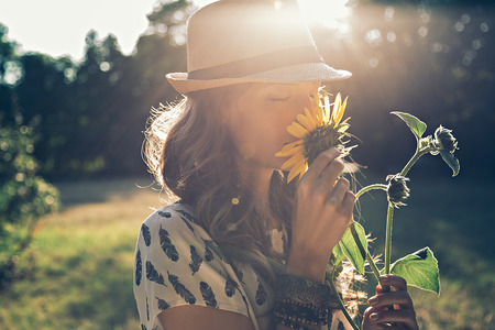 green meadow: Girl smells sunflower in nature Stock Photo
