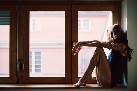 sad lady: Lonely girl in lingerie looking trough the window Stock Photo