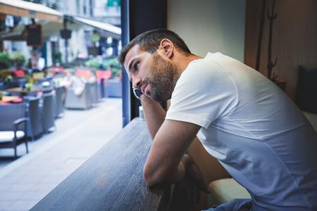 pensando: Hombre de pensamiento por la ventana de la barra Foto de archivo