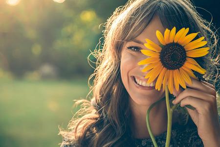 笑みを浮かべて、ひまわりで顔を覆っている公園の少女 写真素材