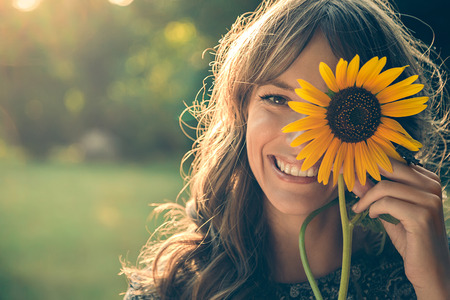 covering: Girl in park smiling and covering face with sunflower Stock Photo