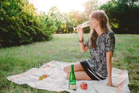 Meisje dat in park fles champagne bekijkt en op iemand wacht