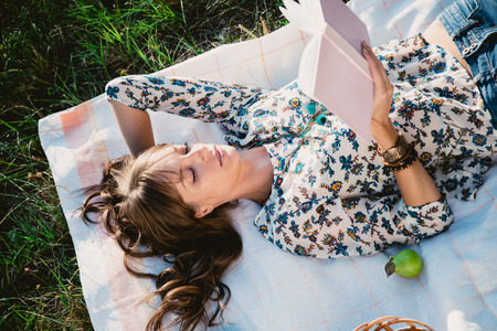 Girl lying in the park and reading a book Standard-Bild