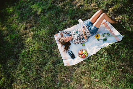 woman laying: Happy girl lying on the grass in a park and reading