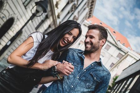 Paar lachen en hand in hand in de stad