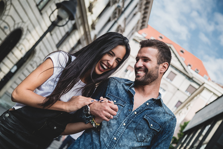 Para śmiejąc się i trzymając się za ręce w mieście