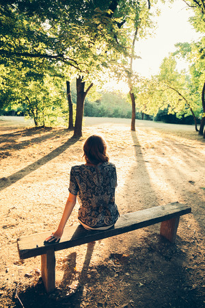 girl sitting: Girl sitting on a park bench facing the sun. From the back Stock Photo