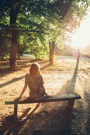 glare: Girl sitting on a park bench facing the sun. Sun glare. From the back